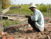Cambodian mason working on a foundation in a rice field