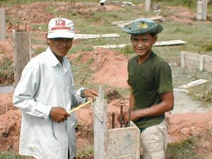 Cambodian concrete workers tie rebar
